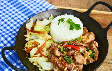 Fried sliced pork with garlic and pepper  served with Fried vegetable and Thai rice in small wok