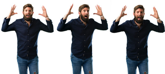 Young man with beard happy and surprised cheering expressing wow gesture isolated over white background