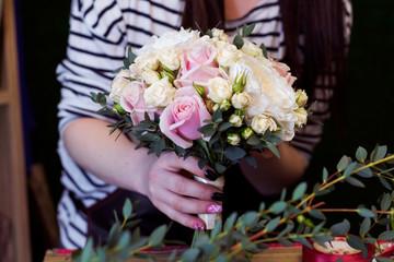 Florist makes bouquet for wedding.