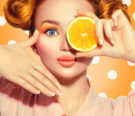 Beauty joyful teenage girl takes juicy oranges. Teen model girl with freckles, funny red hairstyle, yellow makeup and nails on polka dots background