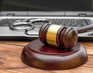 Gavel with laptop and handcuffs on the wooden  table.