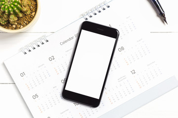 Top view of smart phone isolated white screen for mockup design or app display with calendar on table
