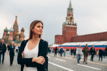 Young beautiful woman is on the Red Squere. Tourism in Russia. She looks around on the Red Squere.