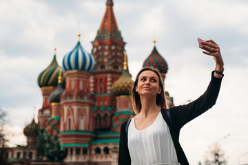 Cute girl makes a selfie with beautiful building. Selfie on the Red Squere. Russian tourism. Old russian architecture.