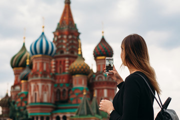 Woman makes a picture of old russian church. Tourism in Moscow. Making picture of beautiful building. Russian architcture