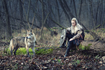 Viking warrior woman with ax and shield, next to an wild wolf, looking for danger, ready to attack
