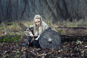 Portrait of dangerous Viking warrior woman with ax and shield in the forest ready to attack - viking female with braided hair and makeup looking aggressive at camera