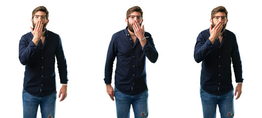 Young man with beard covers mouth in shock, looks shy, expressing silence and mistake concepts, scared isolated over white background