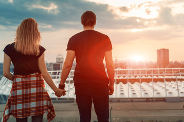 A boy with a girl taking hands on his hands watching the sunset in the evening city. Silhouette of lovers against the background of the city.