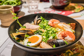 A large bowl of Japanese Ramen with egg, meat, prawn, mussel and vegetable