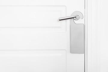 Door knob with empty label on a door handle for your text. Empty white flyer mockup hang on door handle. Leaflet design on entrance doorknob. Dont disturb sign. Hotel room clear hanger. blank