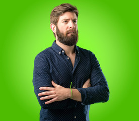 Young hipster man with big beard nervous and scared biting lips looking camera with impatient expression, pensive over green background