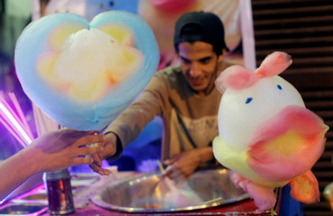 An Egyptian vendor makes traditional sweets and cotton candy in the shape of hearts and cartoon characters in old Cairo
