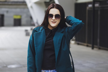 Beautiful brunette girl. Fashionable, stylish with black hair, in coats, jeans and sunglasses