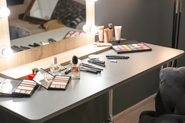 Bottles of perfume and makeup products on dressing table