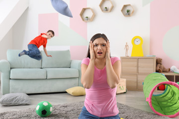 Young nanny in despair and troublesome child at home