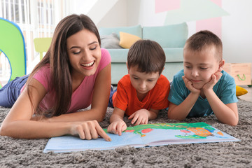 Two little boys reading book with nanny at home
