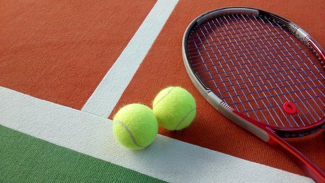 Tennisschläger mit Tennisbällen auf einem Indoor Tennisplatz