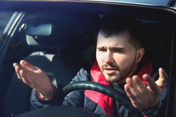 Young man in car during traffic jam
