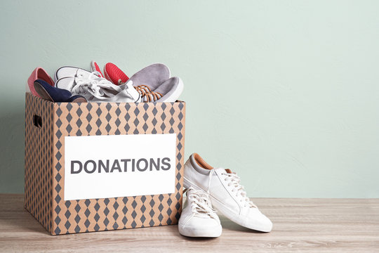 Donation box with shoes on wooden table against color background