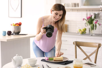 Young blogger taking photo of food in kitchen