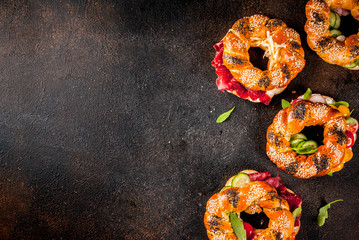 Variety of homemade bagels sandwiches with sesame and poppy seeds, cream cheese,  ham, radish, arugula, cherry tomatoes, cucumbers, dark concrete background copy space above