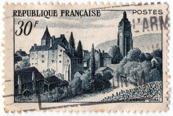 Leeds, England - April 20 2018: an old blue french postage stamp with an image of the town of arbois