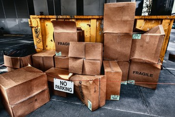 Piles of dirty cardboard boxes next to a grungy yellow garbage dumpster.