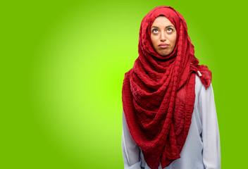 Young arab woman wearing hijab making funny face fooling