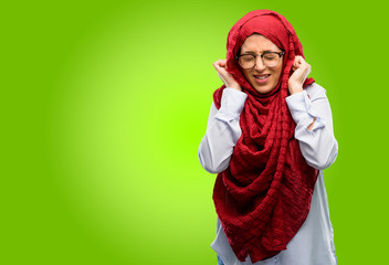 Young arab woman wearing hijab covering ears ignoring annoying loud noise, plugs ears to avoid hearing sound. Noisy music is a problem.