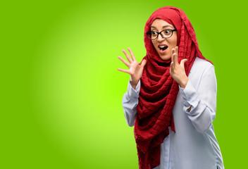 Young arab woman wearing hijab stressful keeping hands on head, terrified in panic, shouting