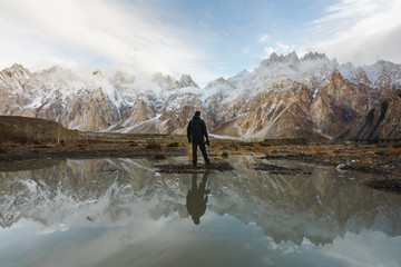 Poster Reflection Photographer looking at Passu Cathedral mountain in Pakistan and reflection on the water