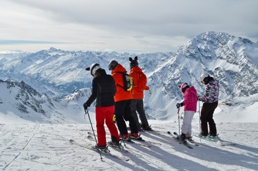 Familie in Skikleidung steht auf Ski, beim Schaufeljoch Panorama des Stubai Gletscher mit Sicht auf die Tiroler Berge