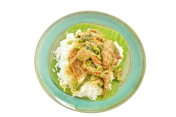 spicy fried duck meat curry with basil leaf and rice on fresh banana leaf