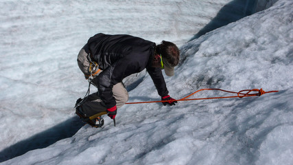 young male mountain climber and guide training ice and rope skills on a glacier on a beautiful summer day