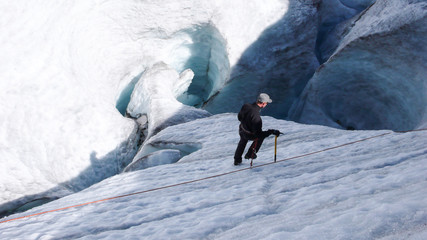mountain climber training rope and ice axe skills on the glacier ice in the Alps near Pontresina
