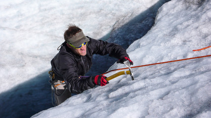 young mountain guide showing and doing training for ice and rope skills on a glacier in the Alps