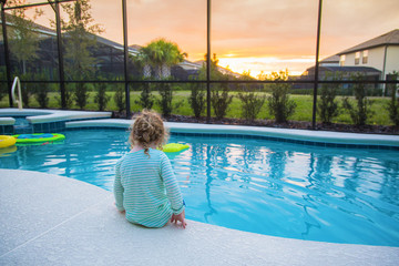 Rear view of a child sitting on the edge of a backyard swimming pool. Concept photo of swimming pool danger and child water safety.