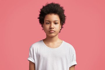 African American schoolboy with curly bushy hairstyle, has serious expression, doesn`t want go to school, dressed casually, looks confidently at camera, isolated over pink background. Childhood