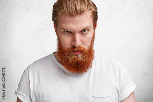 868f4c9ab468 Waist up shot of serious male boss with ginger beard and moustache, has  informal meeting with colleagues, informs about future plans, has stern face,  ...