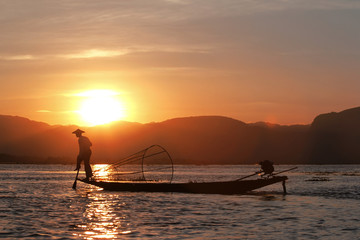 Fisherman silhouette at the sunset on the Inle Lake, Myanmar (Fishermen on the Inle Lake use traditional one-leg rowing technique)