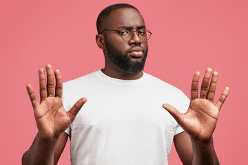 Photo of serious young African American male denies something, expresses his refusement, poses against pink background, rejects participaiting in discussion, has confident look. I don`t want it!