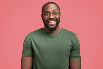 Waist up shot of cheerful dark skinned man being in good mood as dates with beautiful girl, wears casual green t shirt and glasses, isolated over pink background. Satisfied African American guy