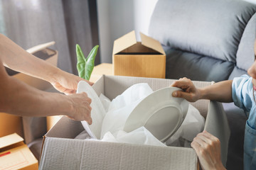Young happy woman moving in new home and unpacking cardboard boxes