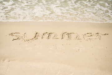 "The inscription on the sand ""Summer"". Beach and waves."