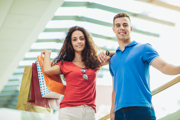 Happy beautiful young couple holding shopping bags and smiling while doing shopping in mall