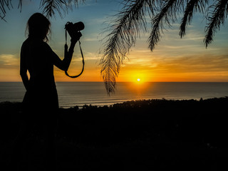 young female traveler on vacation is photographing beautiful kitschy sunset through palm trees