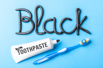 Black toothpaste from charcoal for white teeth. Word BLACK from  toothpaste,  tube and  dental counter on  blue background.