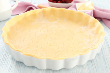 Baking pan with unbaked crust for cherry pie on kitchen table
