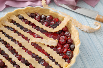 Baking pan with unbaked cherry pie on kitchen table